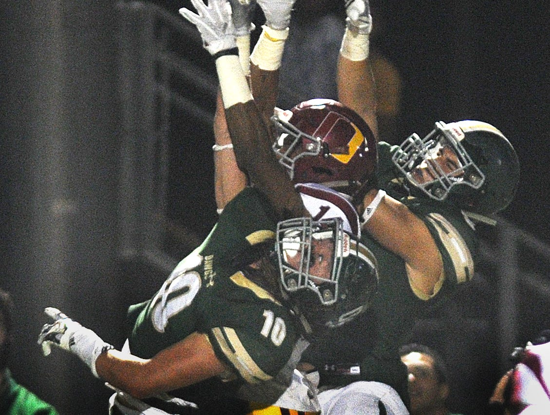 Oxnard's Aaron Fontez, center, battles for the ball against two South Hills receivers during Saturday night's Division 6 championship game. South Hills caught the deflected pass. Oxnard lost the game, 24-13.