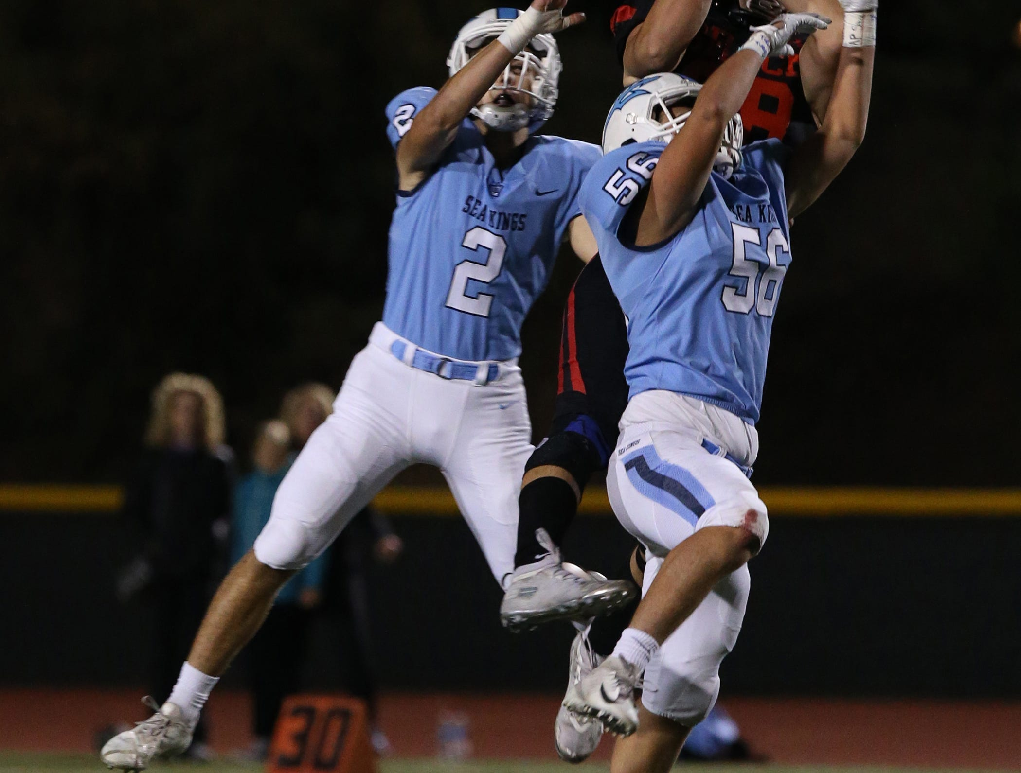 Grace Brethren's Avery Cook makes a spectacular catch between Corona del Mar's Jack Elliott and Cole Rener during the Lancers' 26-14 win in the CIF-SS Division 4 championship game Saturday night at Royal High.