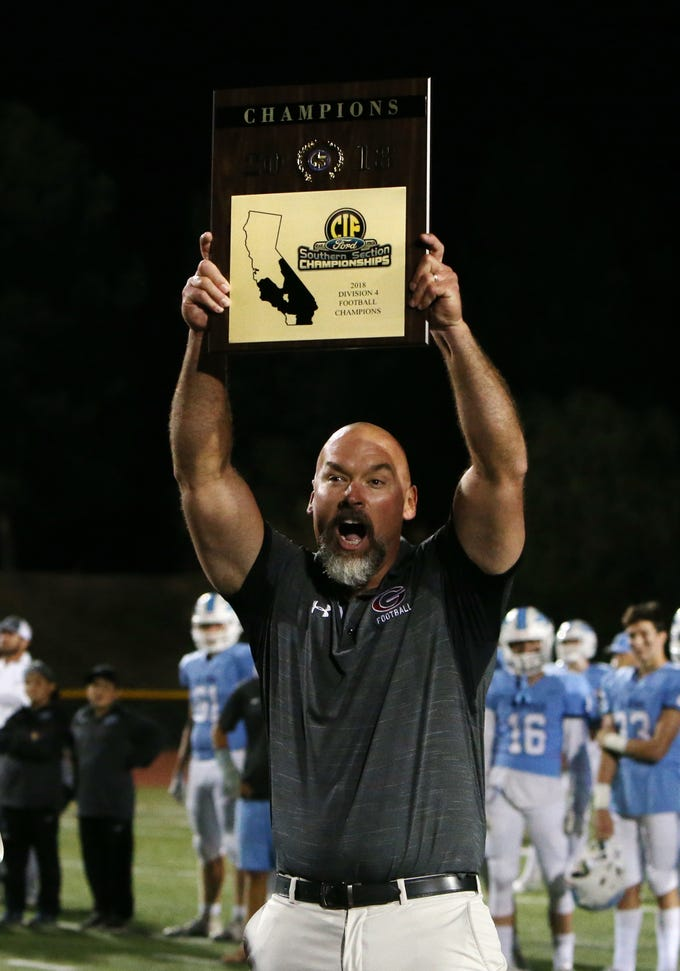Grace Brethren head coach Josh Henderson holds up the 2018 CIF-Southern Section Division 4 championship plaque after the Lancers defeated Corona del Mar 26-14 at Royal High on Saturday night.