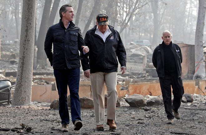 In this Nov. 17 photo, President Donald Trump talks with Gov.-elect Gavin Newsom, left, as California Gov. Jerry Brown walks at right during a visit to a neighborhood destroyed by the Camp wildfire in Paradise.