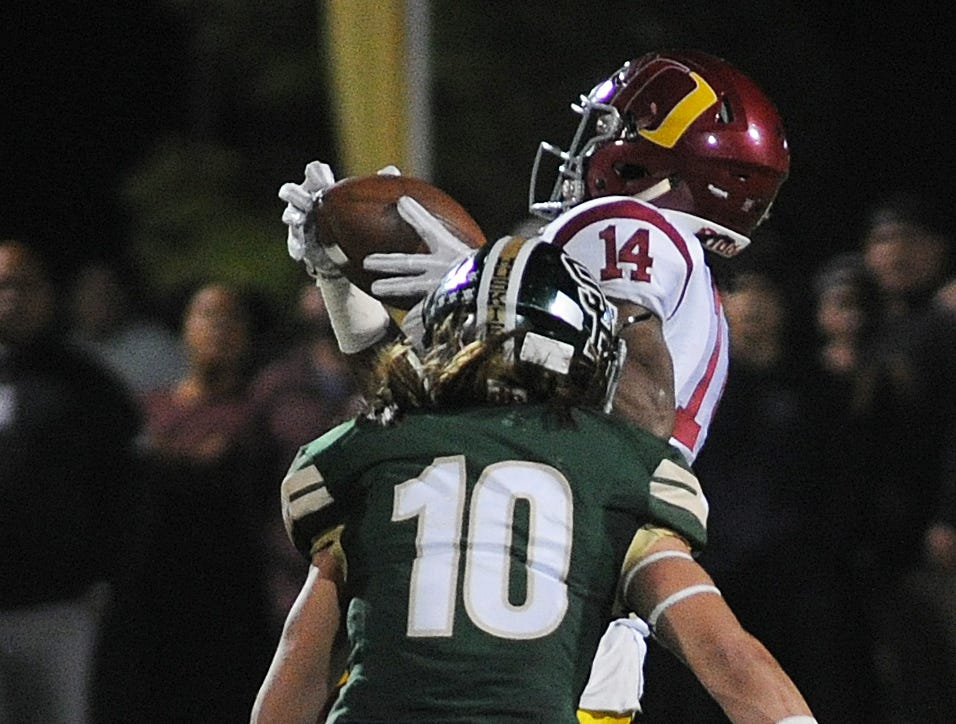 Oxnard High's Aaron Fontez catches a deep pass behind Justin Armendariz of South Hills during the CIF-Southern Section Division 6 championship game at Covina District Stadium on Saturday night. Oxnard lost, 24-13.