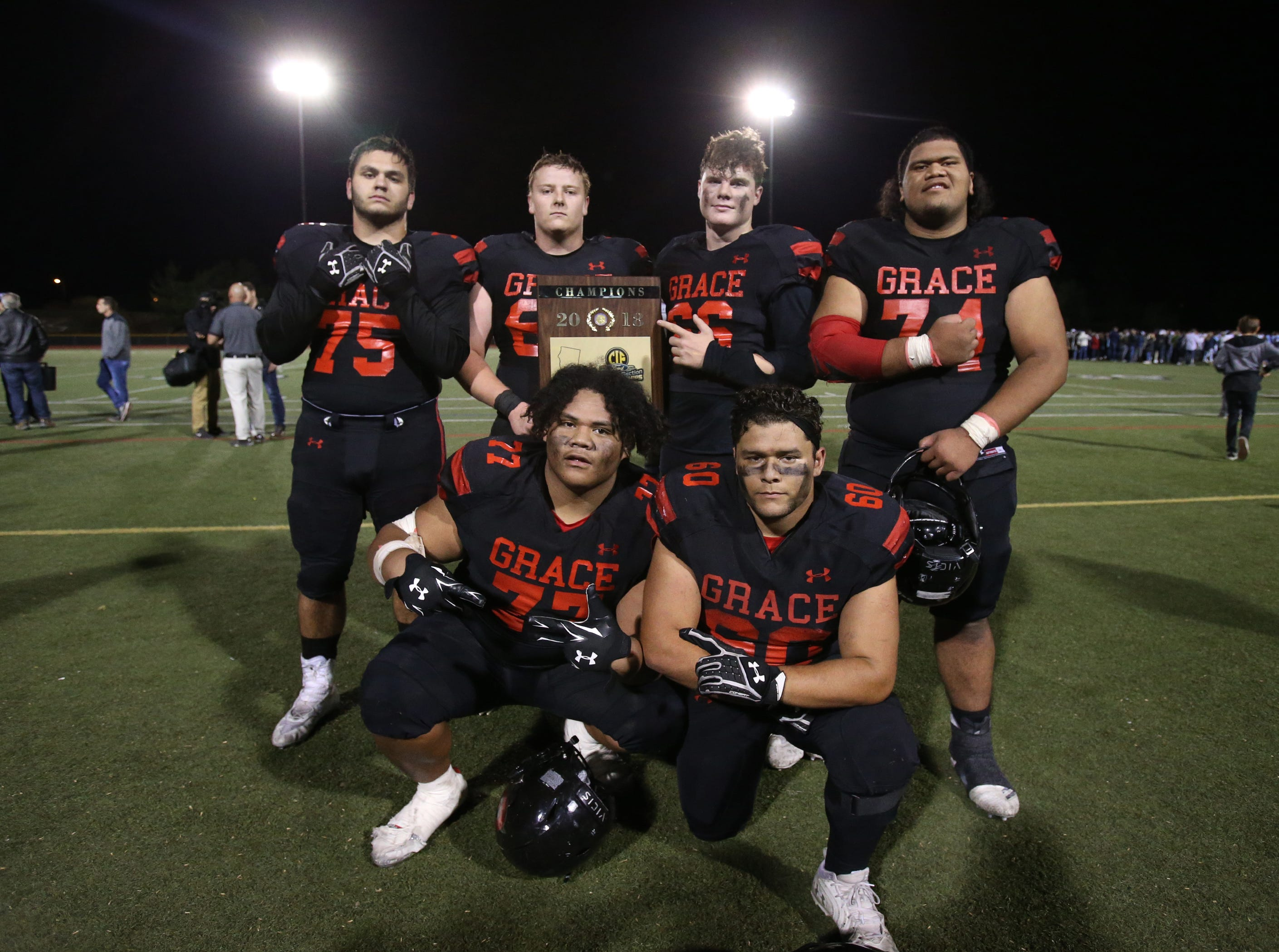 Some of the players on Grace Brethren's defensive line pose with the CIF-SS Division 4 championship plaque after the Lancers defeated Corona del Mar 26-14 at Royal High on Saturday night.