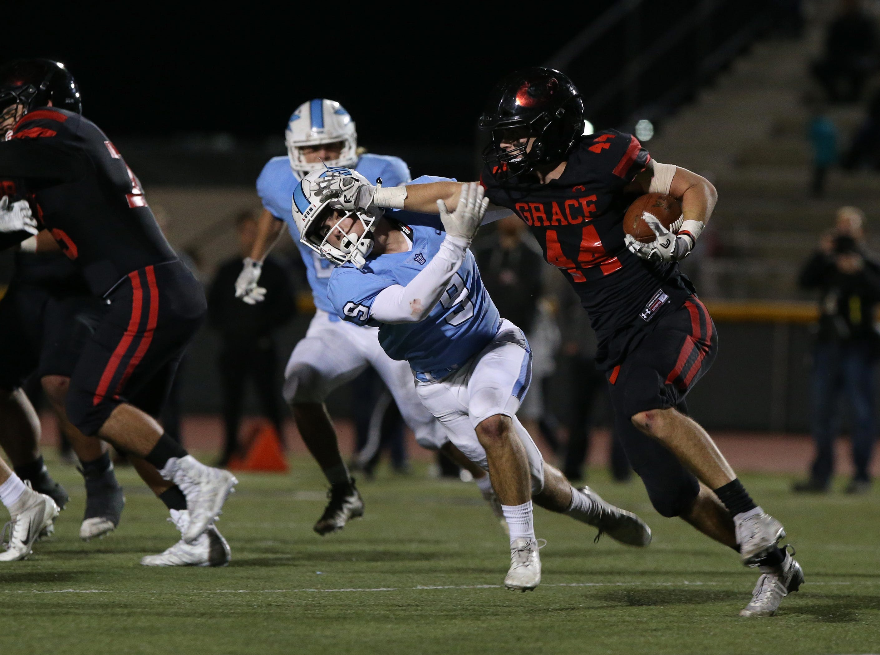 Grace Brethren's Josh Henderson pushes Corona del Mar's Luke Fisher out of the way during the Lancers' 26-14 win over Corona del Mar in the CIF-SS Division 4 championship game Saturday night at Royal High.