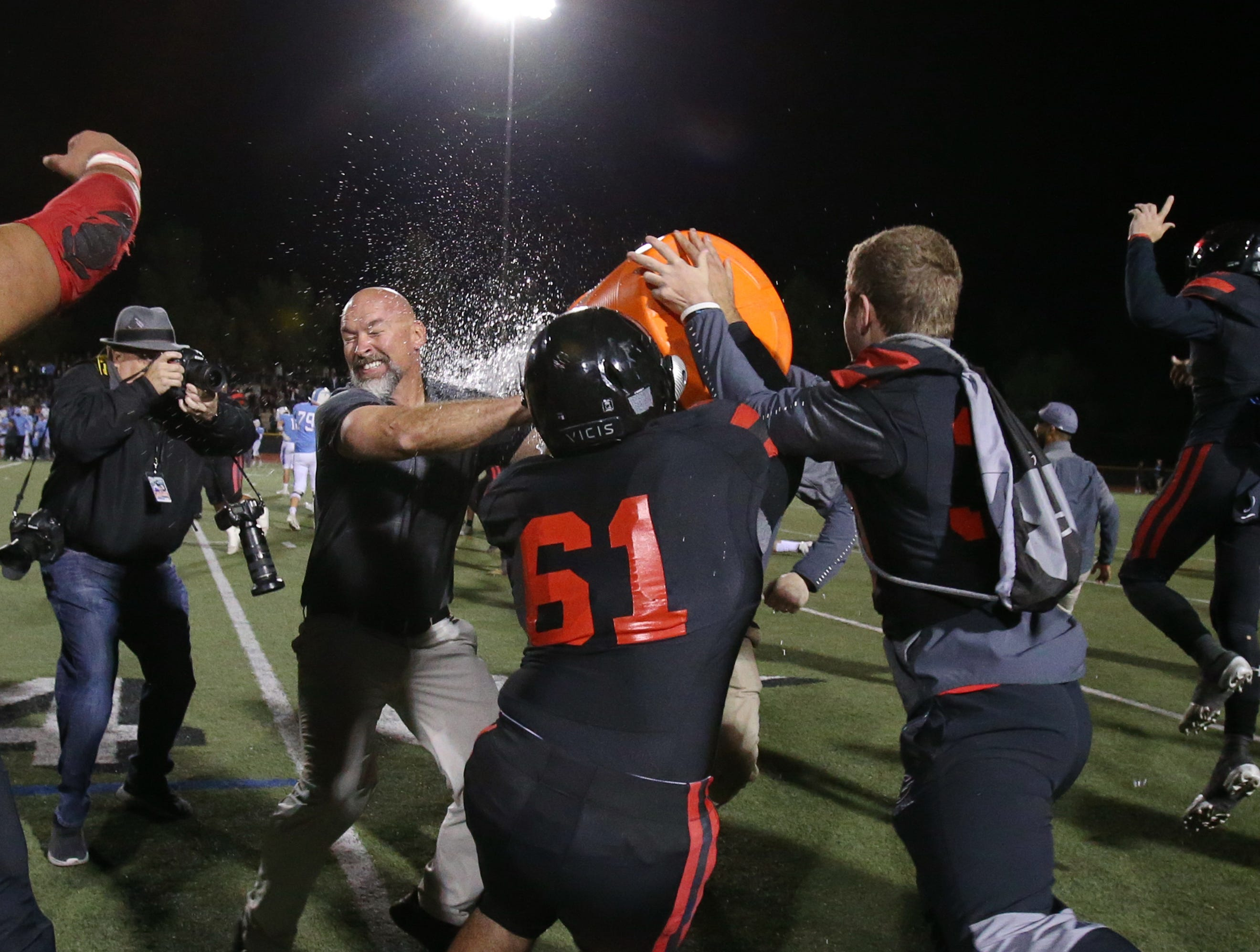 Grace Brethren head coach Josh Henderson gets a Gatorade shower after the Lancers defeated Corona del Mar 26-14 at Royal High on Saturday night to capture the CIF-Southern Section Division 4 championship. It was the second straight CIF title for Grace Brethren, which won the Division 8 title last season.
