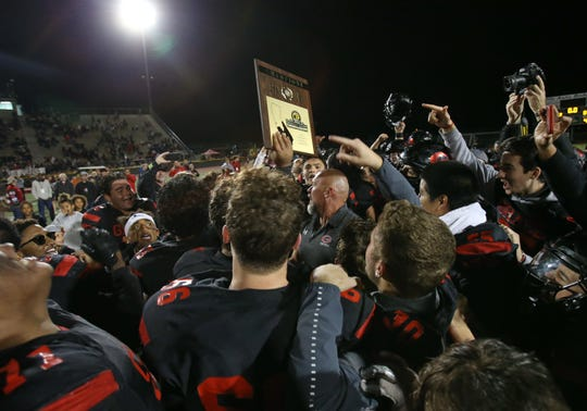 The Grace Brethren team surrounds head coach Josh Henderson after the Lancers defeated Corona del Mar 26-14 at Royal High on Saturday night to capture the CIF-Southern Section Division 4 championship. It was the second straight CIF title for Grace Brethren, which won the Division 8 title last season.