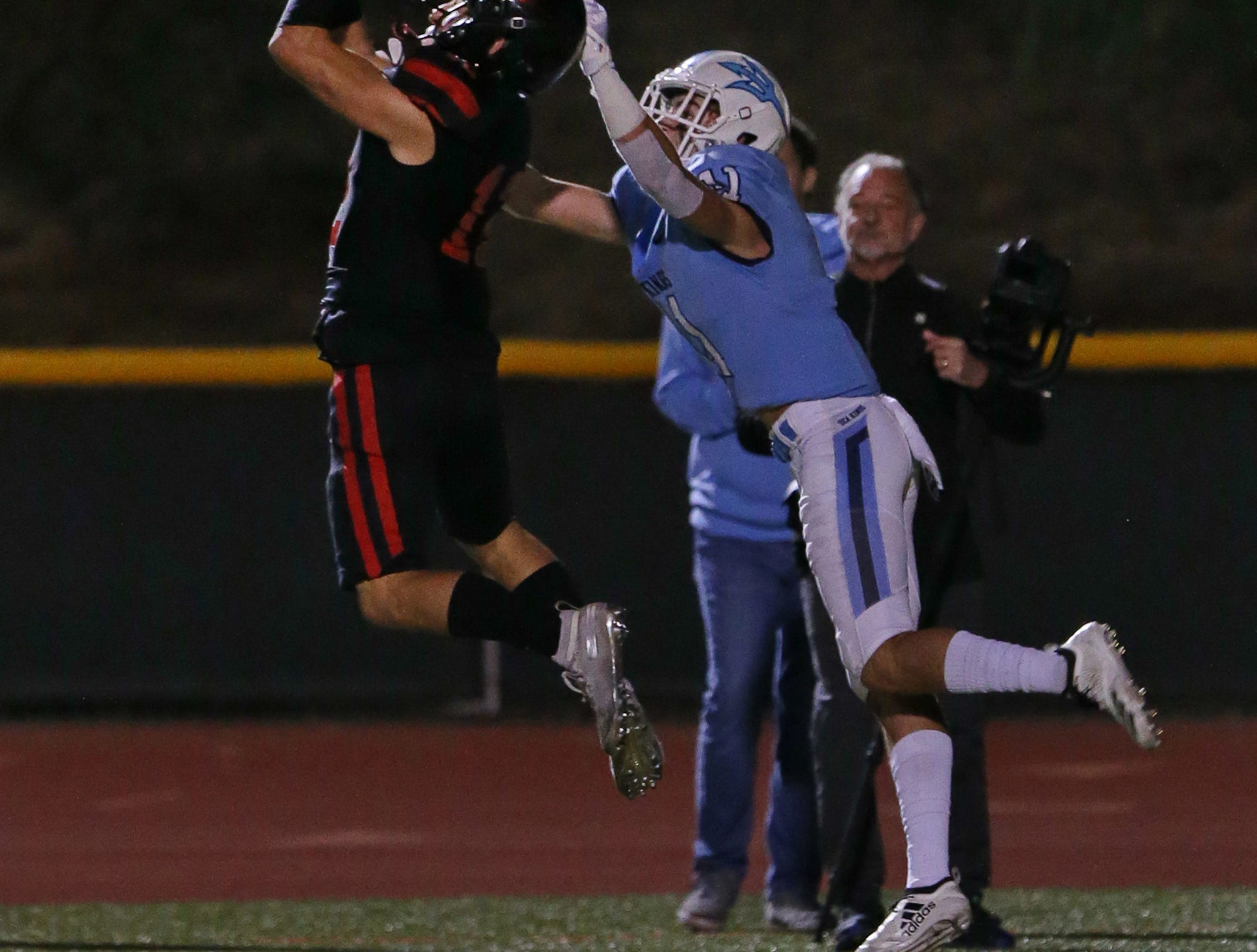 Grace Brethren's Troy Hothan makes an interception in front of Corona del Mar's Bradley Schlom in the end zone to seal the Lancers' 26-14 win in the CIF-SS Division 4 championship game Saturday night at Royal High.