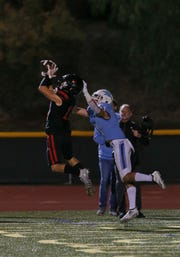 Grace Brethren's Troy Hothan makes an interception in front of Corona del Mar's Bradley Schlom during the Lancers' 26-14 win in the CIF-SS Division 4 championship game last Saturday night. The Lancers will play St. Augustine in the CIF-State Division 2AA SoCal Regional championship game Friday night at Cal Lutheran.