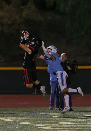 Grace Brethren's Troy Hothan makes an interception in front of Corona del Mar's Bradley Schlom in the end zone in the CIF-SS Division 4 championship game. The Lancers will go for the state title Friday night.