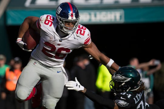 New York's Saquon Barkley (26) holds off Philadelphia's Cre'Von LeBlanc (34) Sunday at Lincoln Financial Field. The Eagles defeated the Giants 25-22.