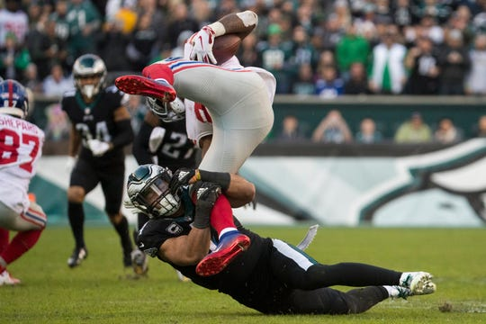 Eagles' Kamu Grugier-Hill (54) sends New York's Wayne Gallman Jr. airborne for a loss Sunday at Lincoln Financial Field. The Eagles defeated the Giants 25-22.