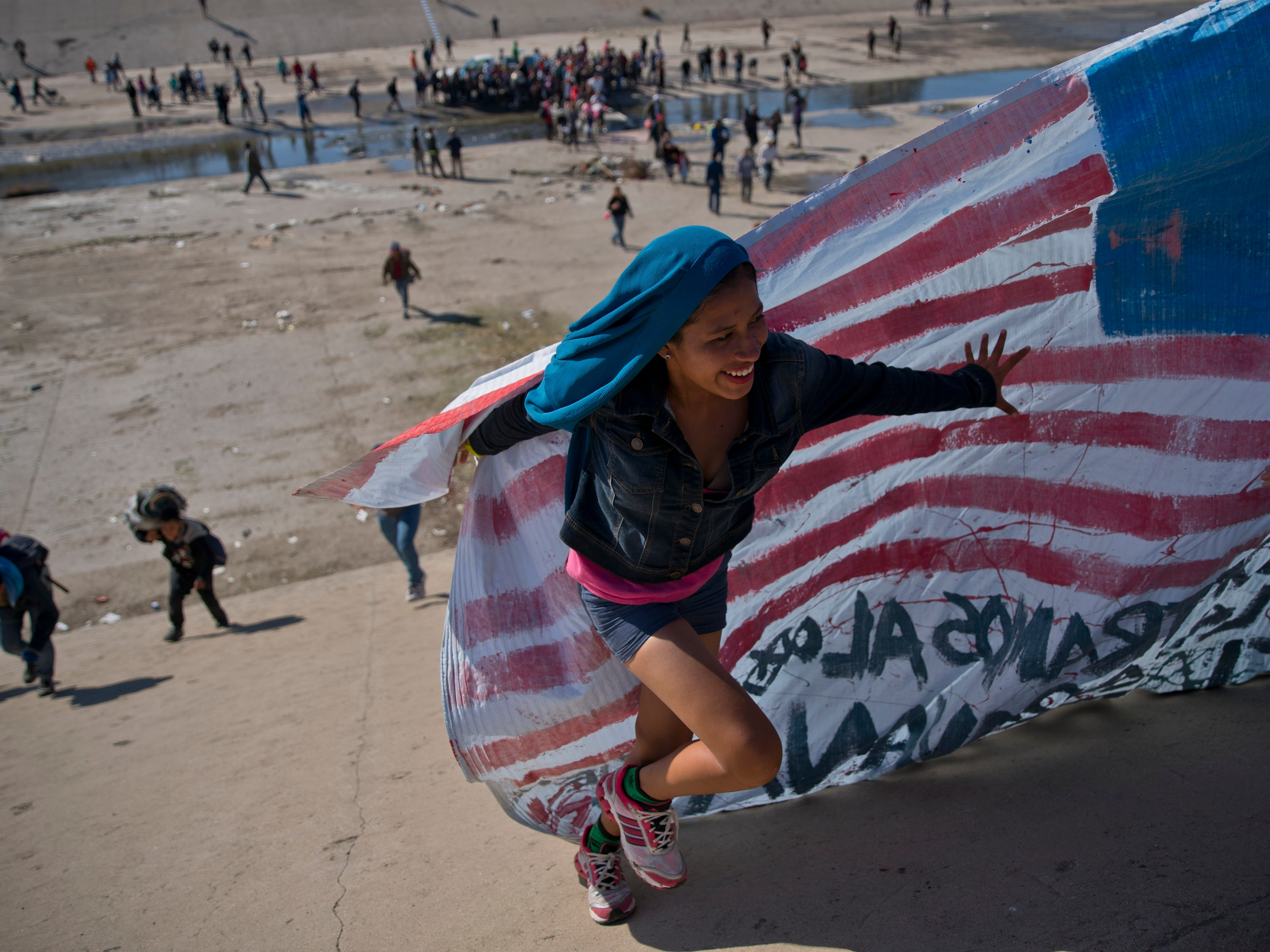 A migrant woman helps carry a handmade U.S. flag up the riverbank at the Mexico-U.S. border after getting past Mexican police at the Chaparral border crossing in Tijuana, Mexico, on Nov. 25, 2018, as a group of migrants tries to reach the U.S.