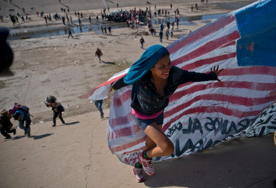 A migrant woman helps carry a handmade U.S. flag up the riverbank at the U.S.-Mexican border after getting past Mexican police at the Chaparral border crossing in Tijuana.