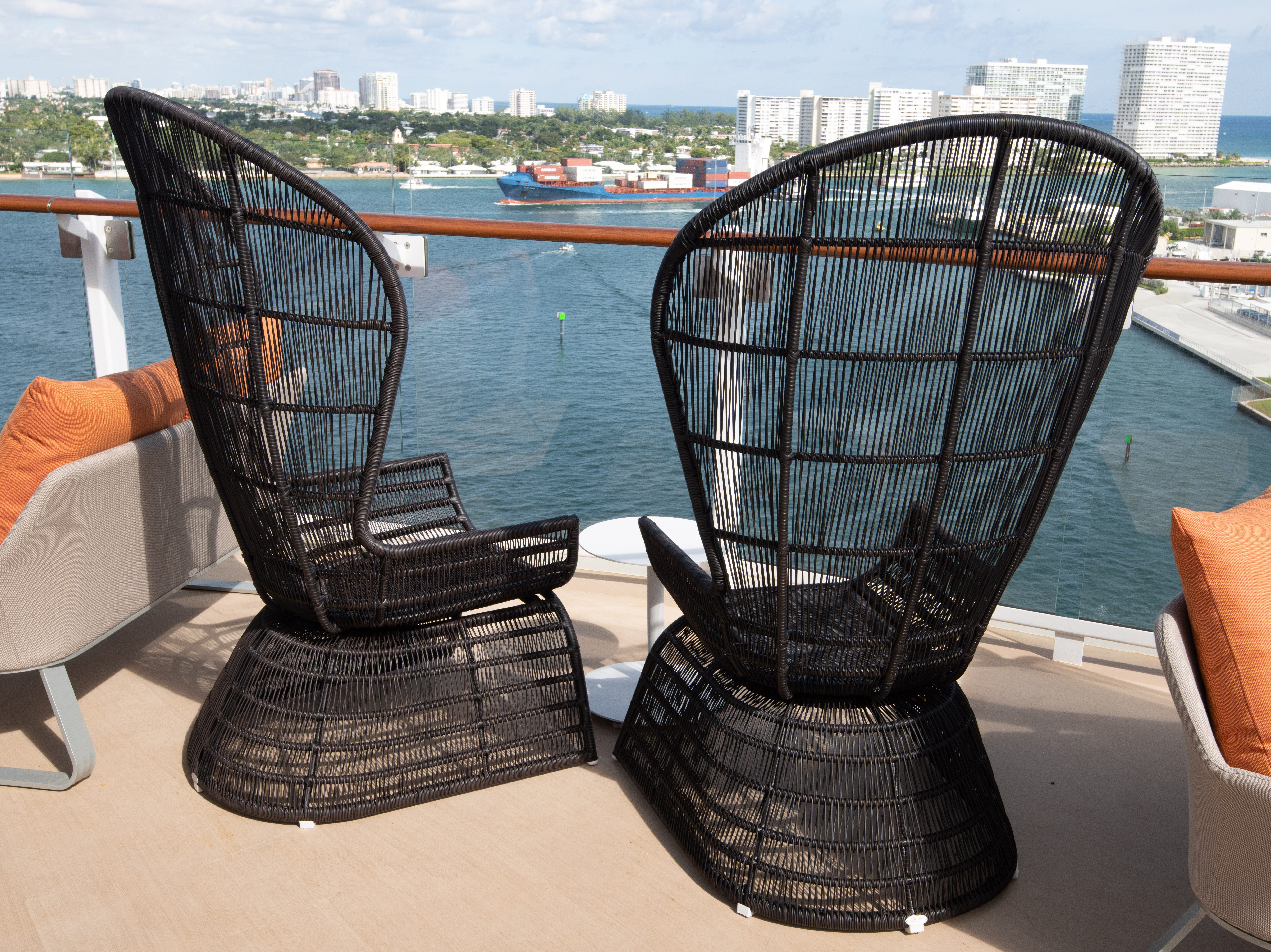 Two black wicker chairs face aft from Celebrity Edge's Sunset Bar area.