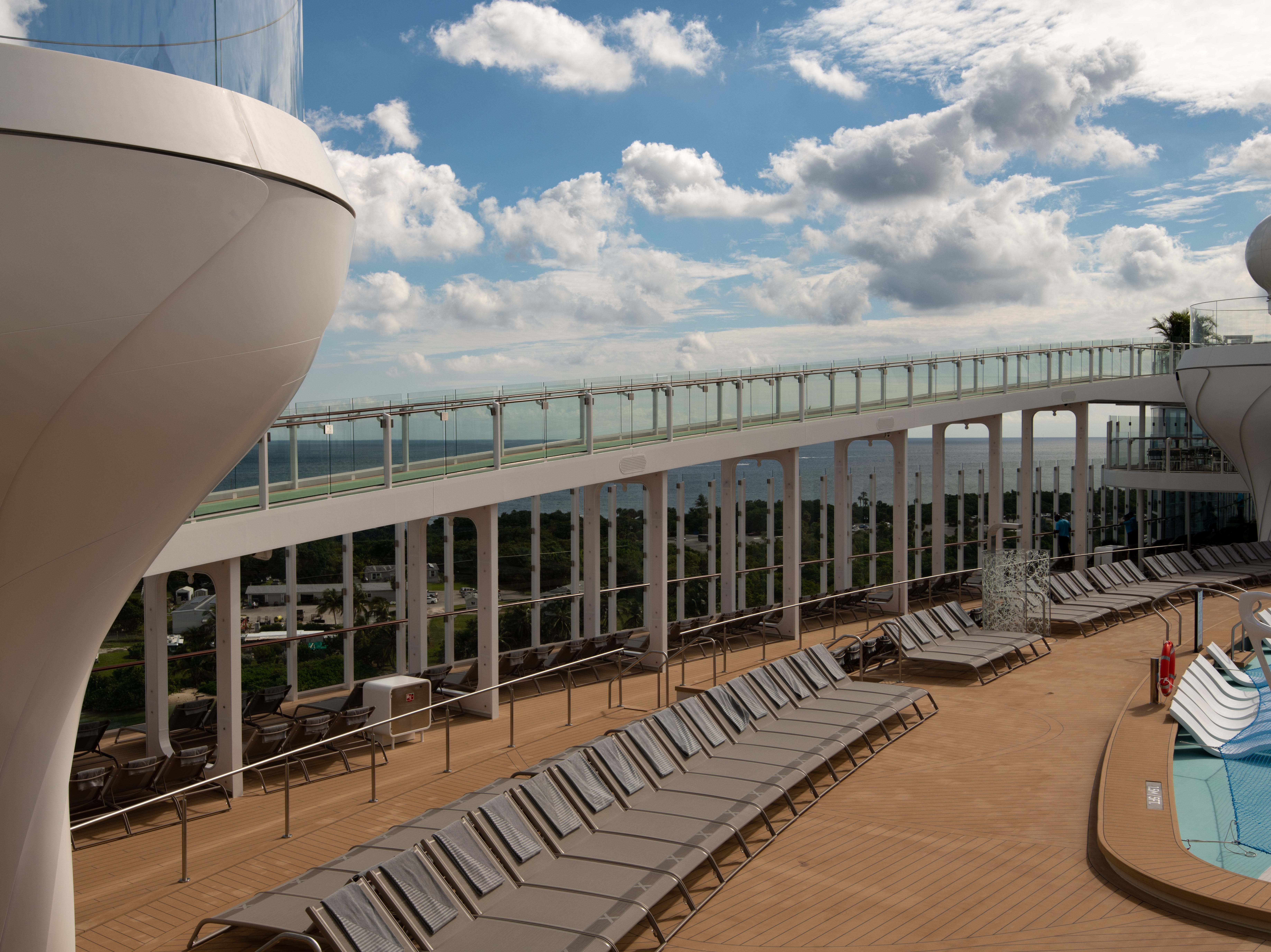 Celebrity Edge's Pool Deck is unusual in its openness to the sea. Soaring, wall-to-wall glass lines its sides, which also feature an asymmetrical jogging track.