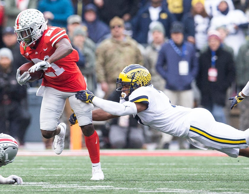 Ohio State wide receiver Parris Campbell breaks a tackle against Michigan linebacker Khaleke Hudson.