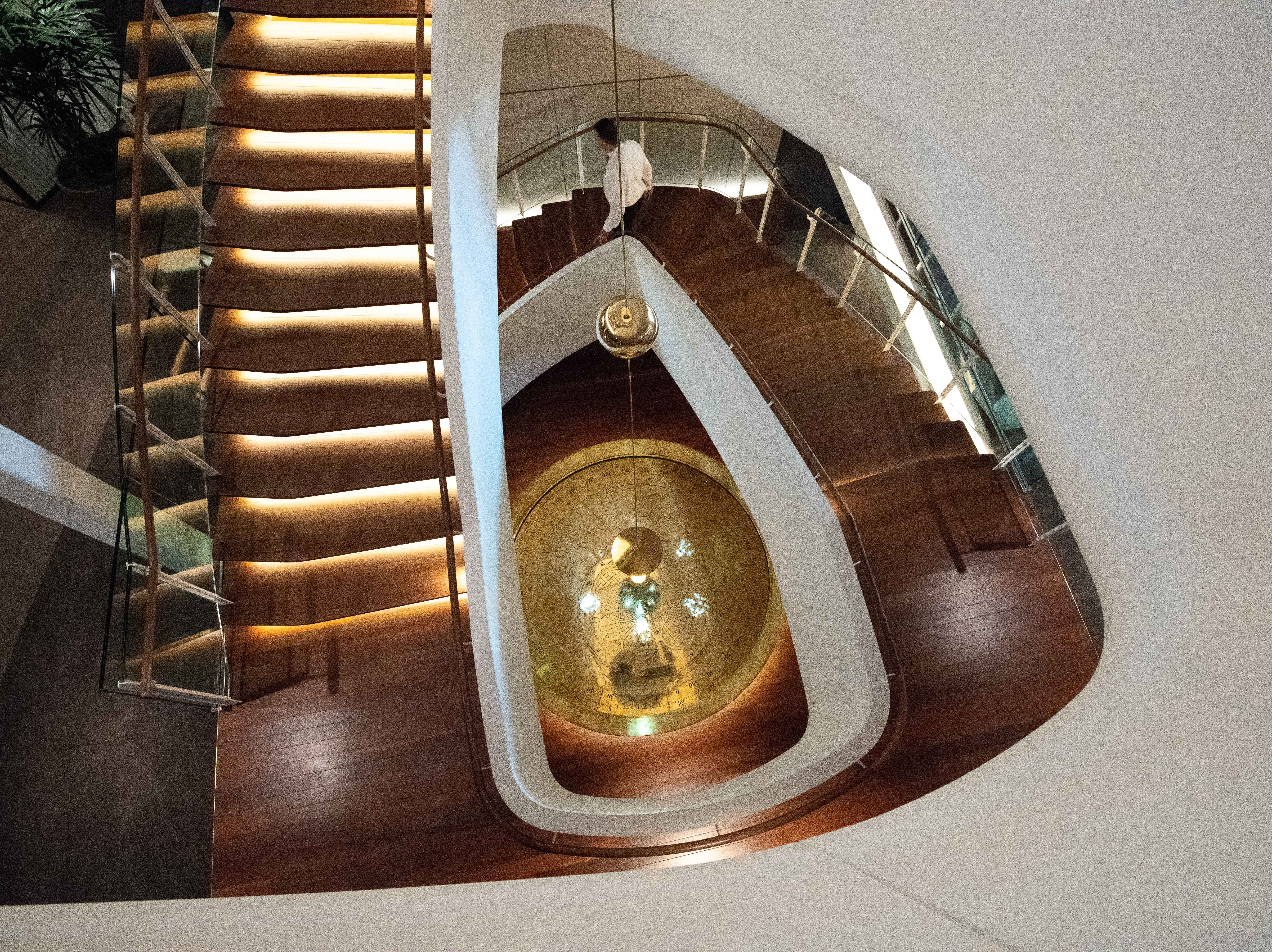 A pendulum occupies the center of a curving staircase that winds down between the main restaurants on Celebrity Edge.