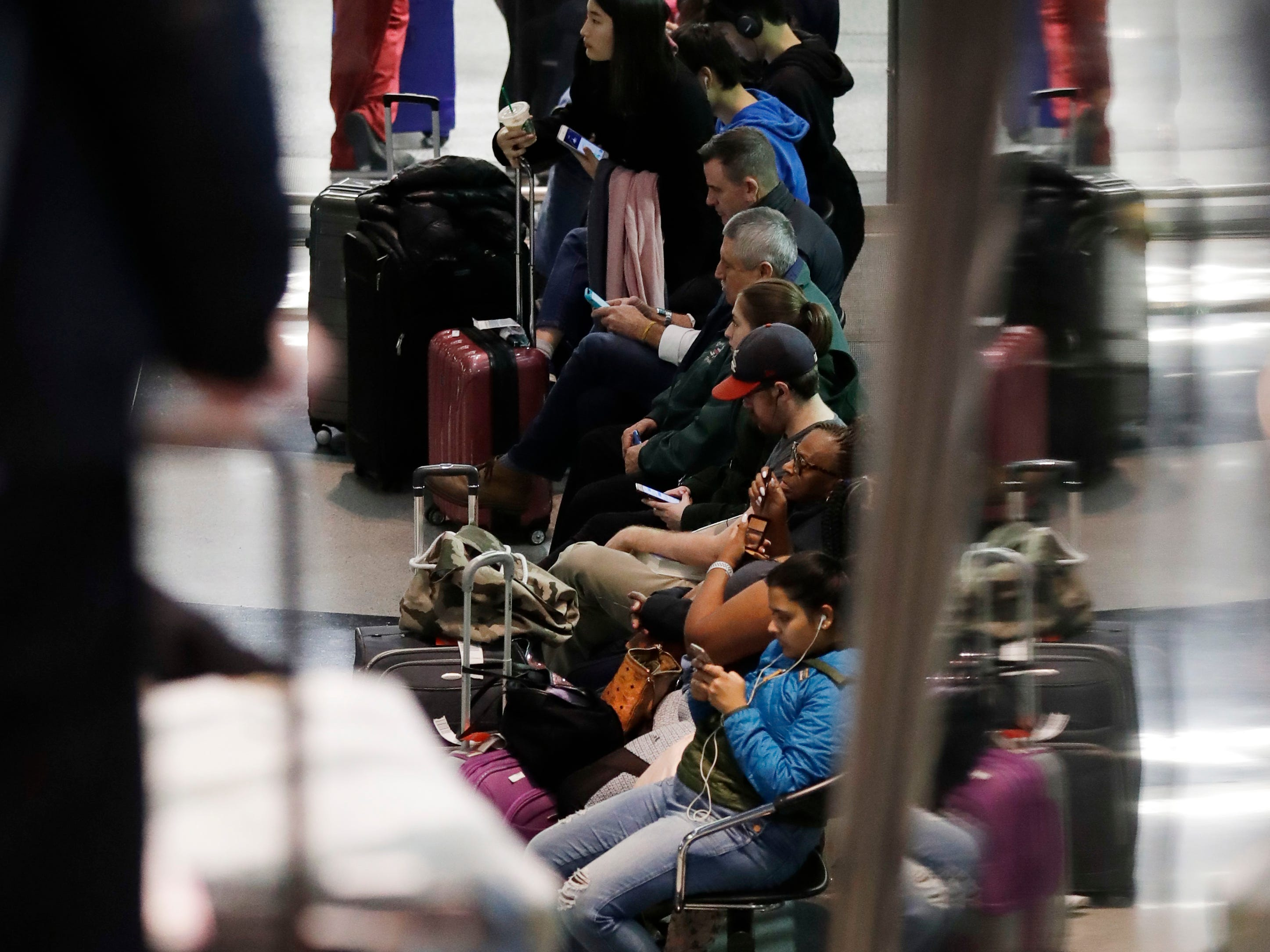 Passengers sit as they wait for their flight at O'Hare airport in Chicago, Sunday, Nov. 25, 2018.
