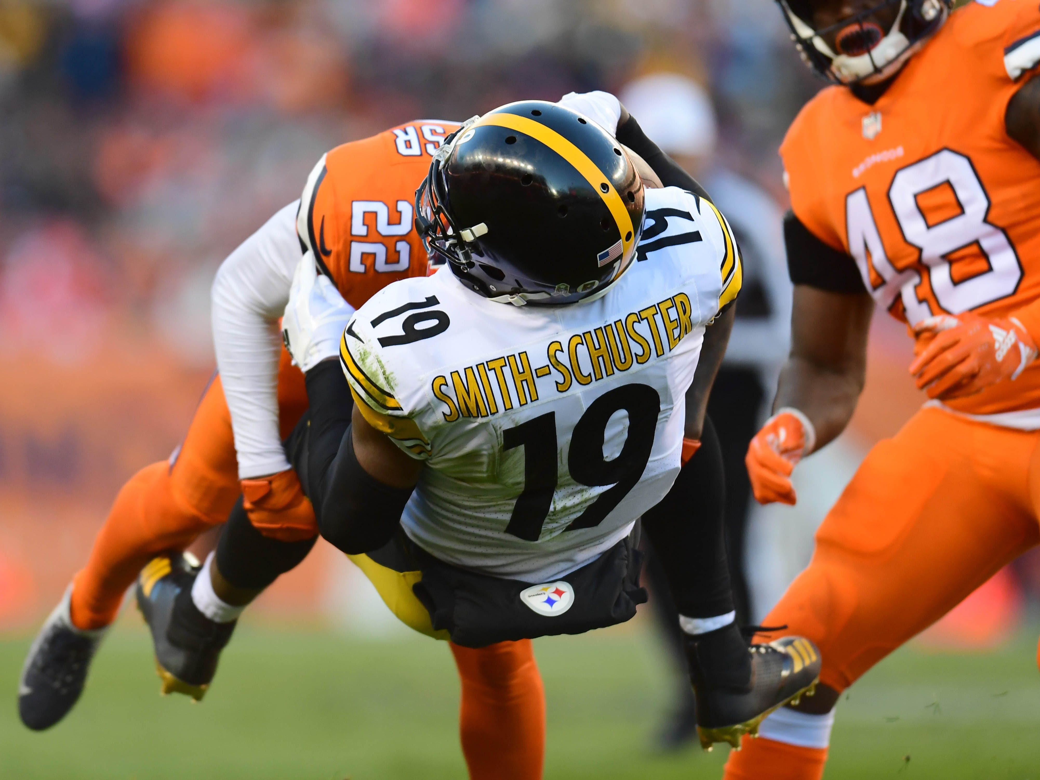 Pittsburgh Steelers wide receiver JuJu Smith-Schuster is tackled by Denver Broncos defensive back Tramaine Brock in a Week 12 matchup at Broncos Stadium at Mile High.