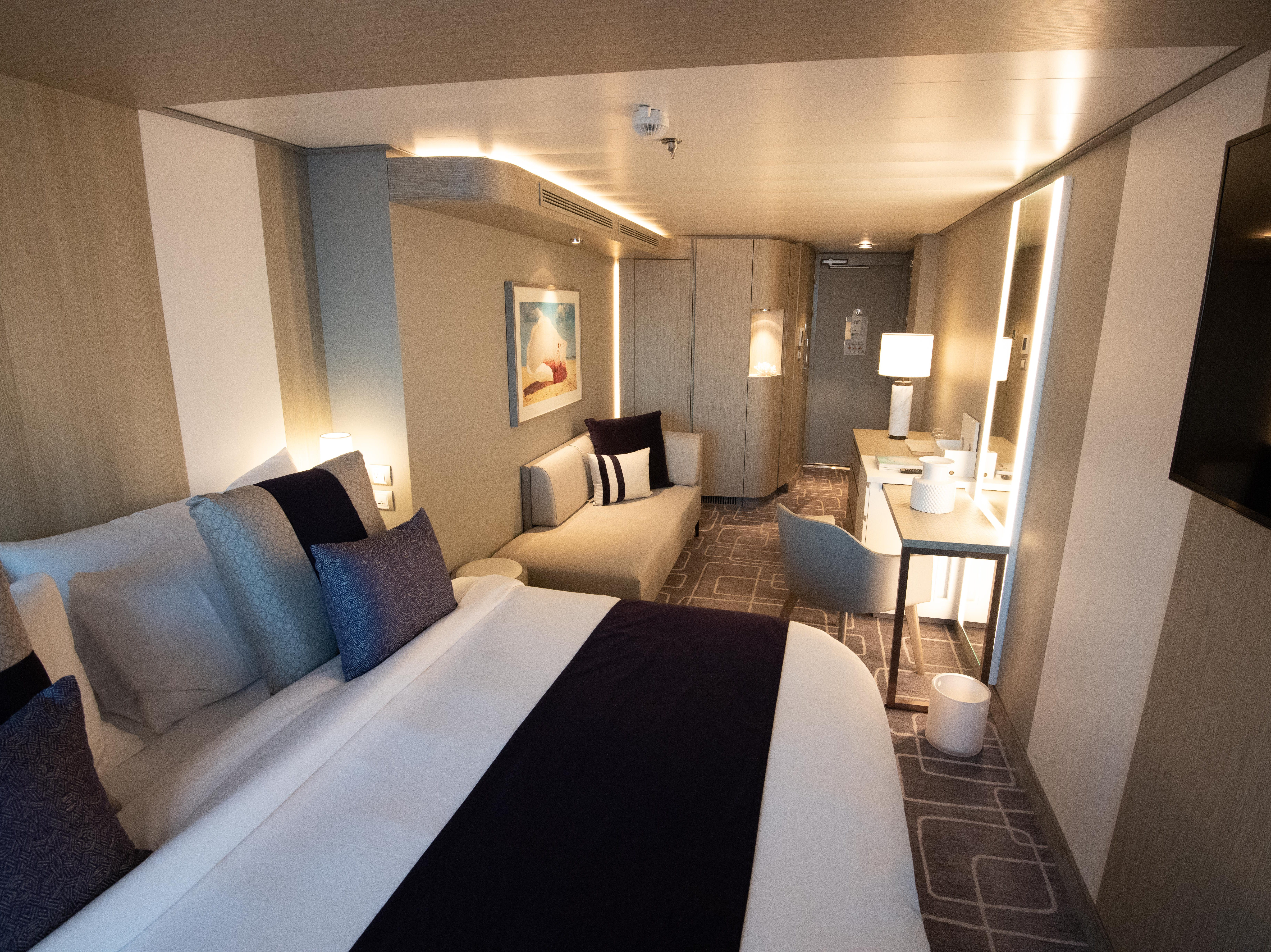 An Edge Stateroom with Infinite Veranda cabin as seen looking back from the balcony area.