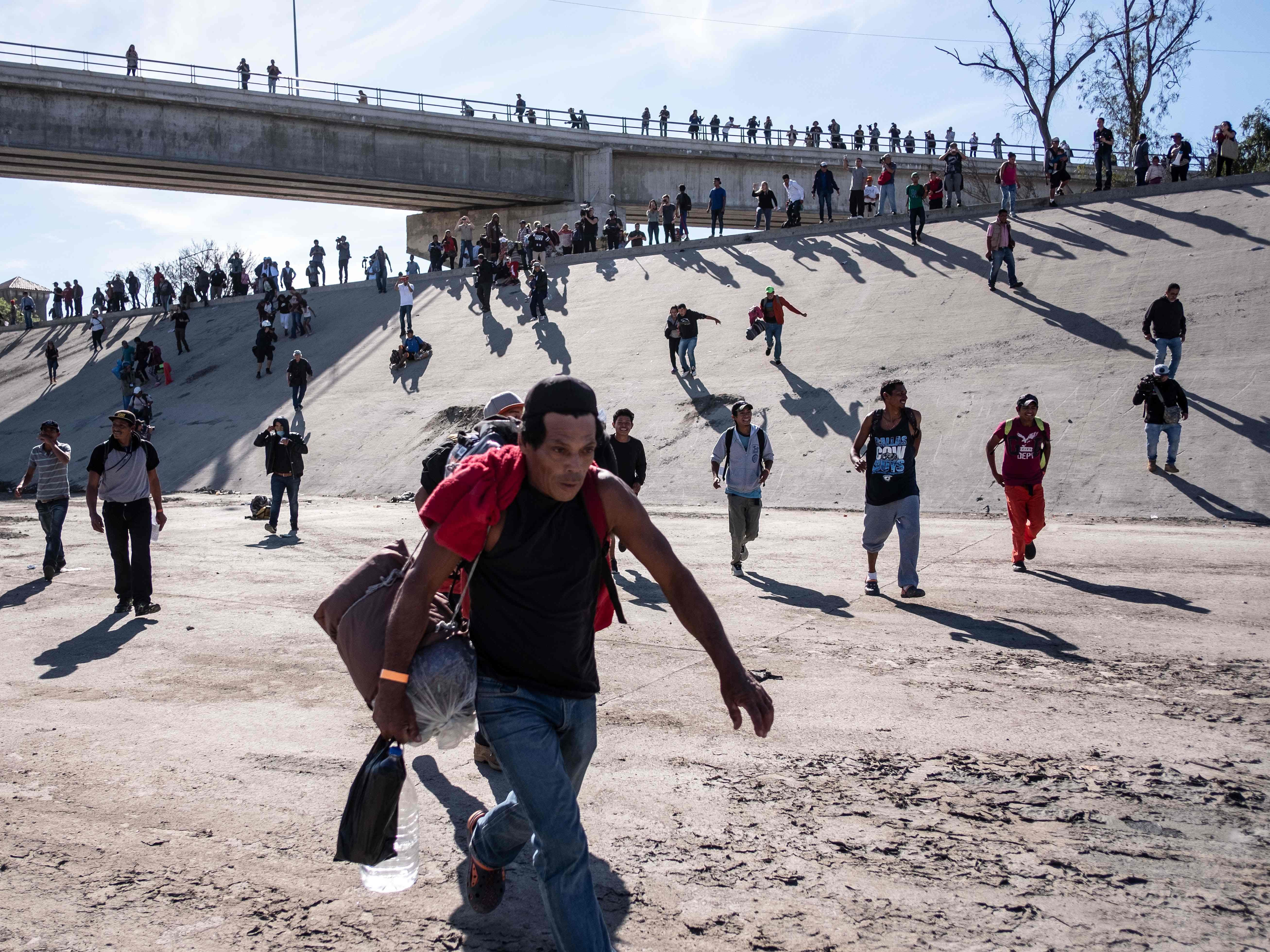 A group of Central American migrants run along the dry riverbed of the Tijuana River in an attempt to get to El Chaparral port of entry, in Tijuana, Mexico, near the US-Mexico border, Nov. 25, 2018. Hundreds of migrants attempted to storm a border fence separating Mexico from the U.S. on Sunday amid mounting fears they will be kept in Mexico while their applications for a asylum are processed.