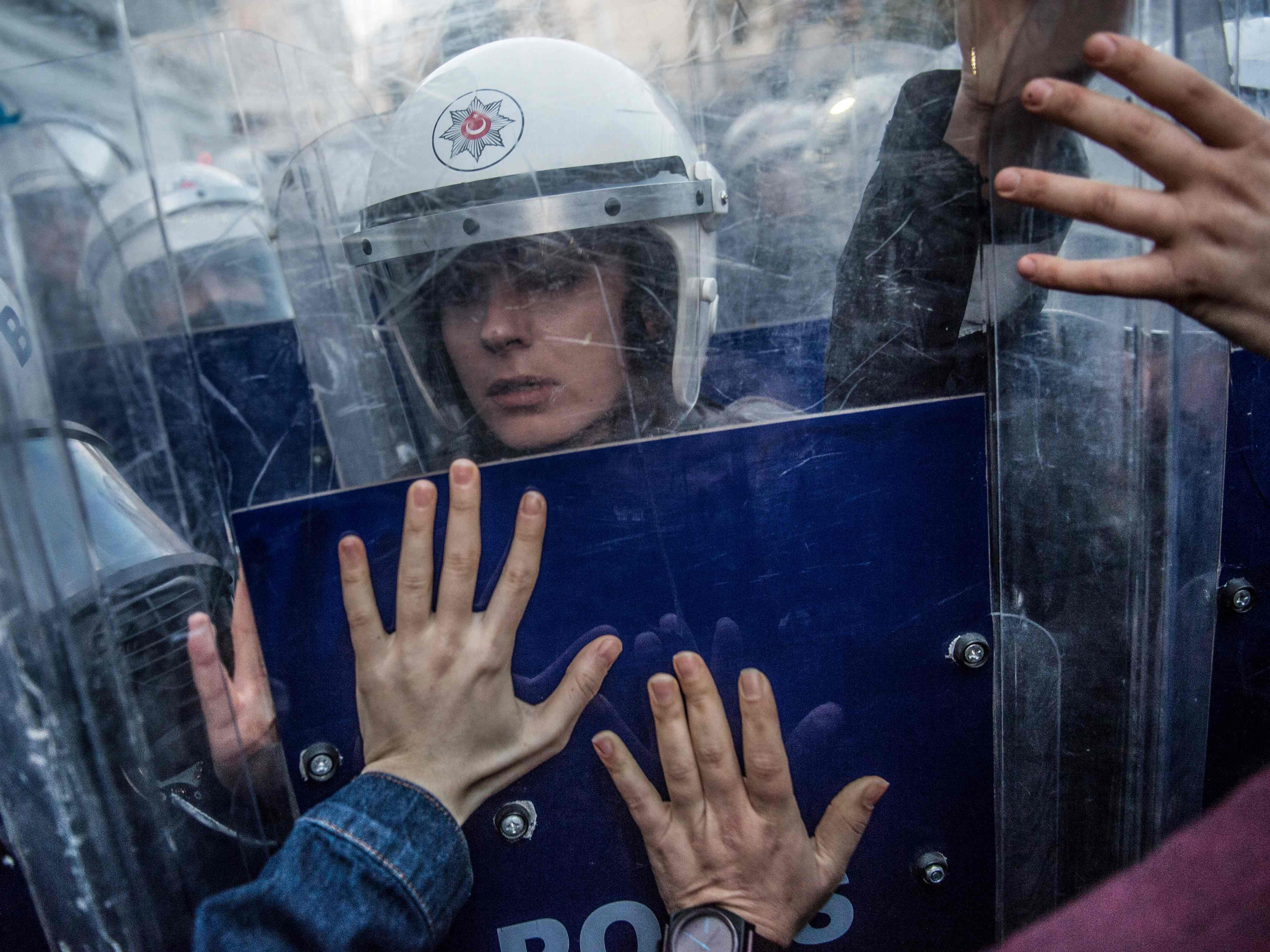 A Turkish female riot police officer reacts during clashes with women's rights activists as they try to march to Taksim Square to protest against gender violence in Istanbul, on November 25, 2018, on the International Day for the Elimination of Violence against Women.