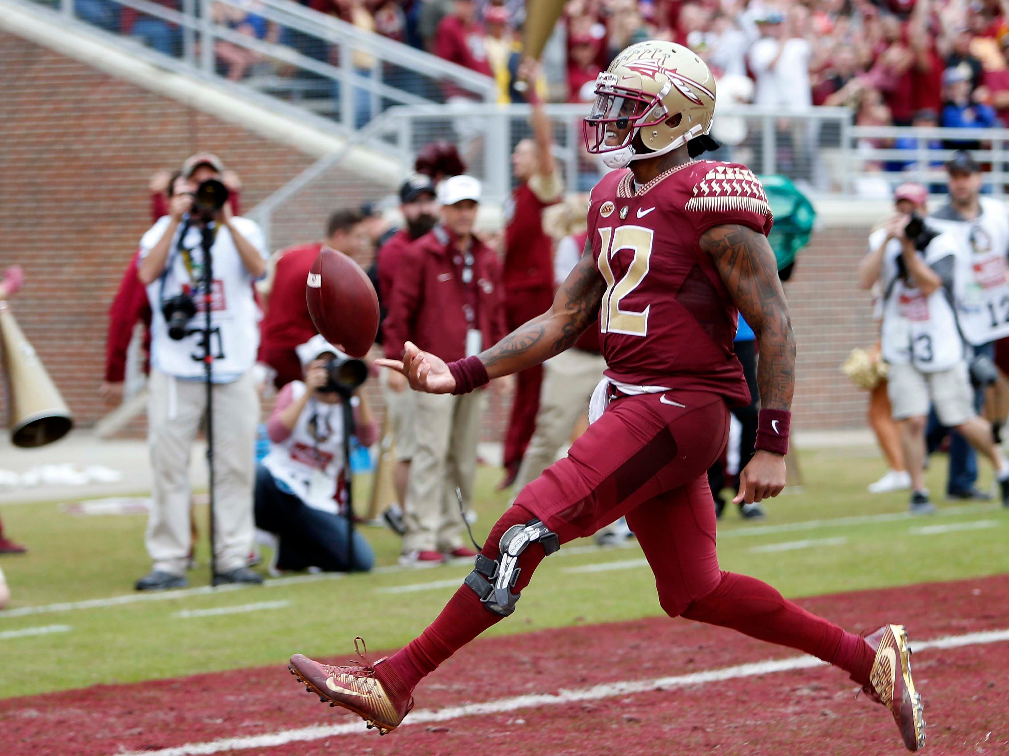 Florida State Seminoles quarterback Deondre Francois (12) flips the ball to an official after scoring against the Florida Gators during the second-half action at Doak Campbell Stadium.