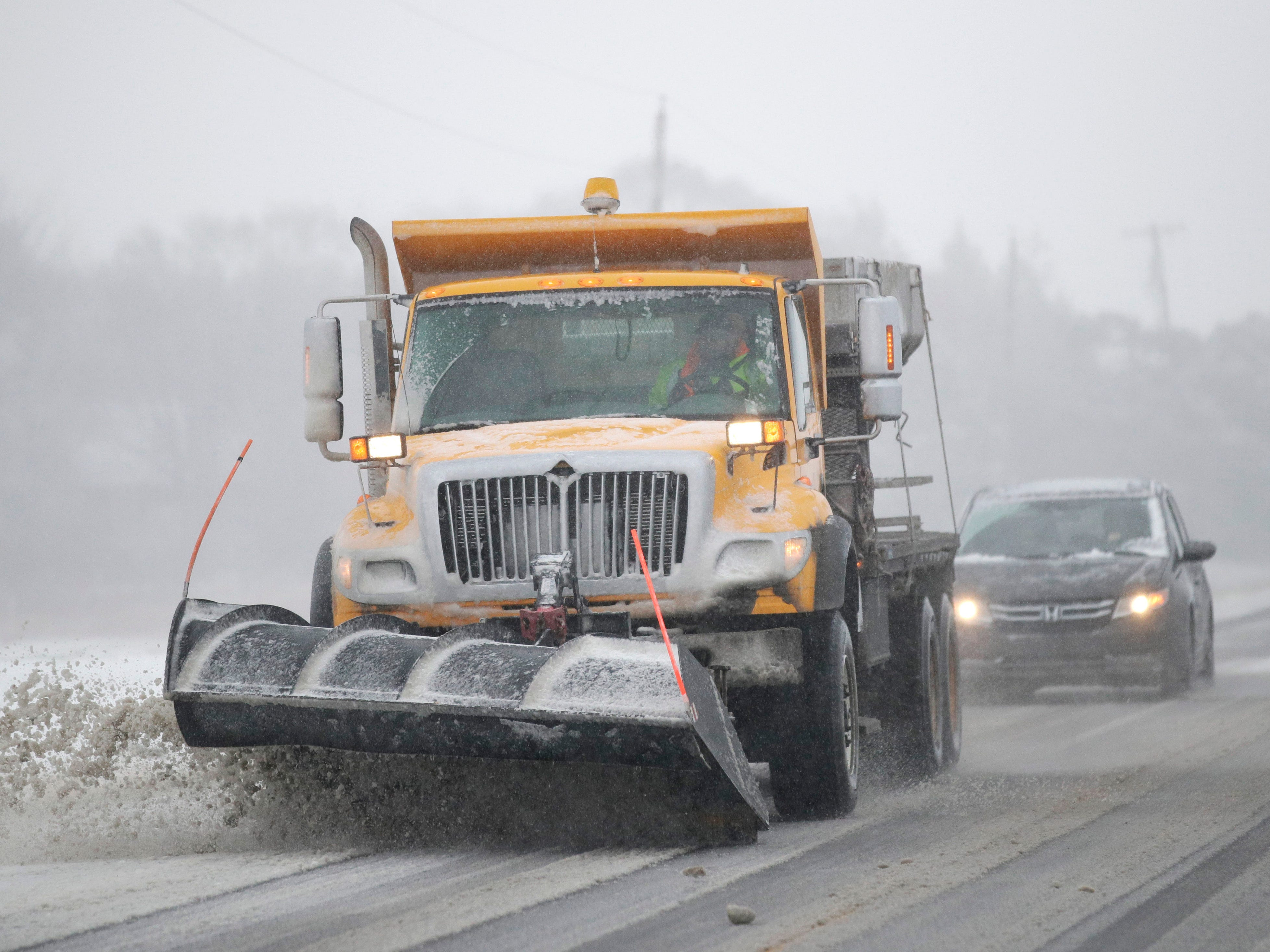 A plow clears snow from Road 438 in Douglas County near Lawrence, Kan., Sunday, Nov. 25, 2018.