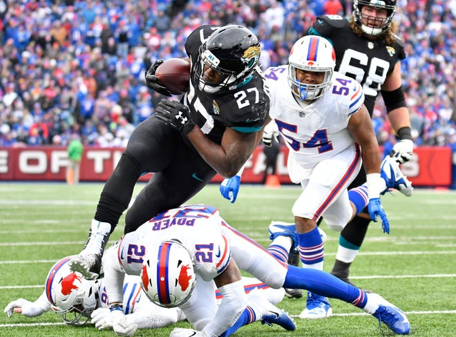 Jacksonville Jaguars running back Leonard Fournette (27) runs the ball down to the one yard line as Buffalo Bills free safety Jordan Poyer (21)and defensive end Eddie Yarbrough (54) defend during the second quarter at New Era Field.