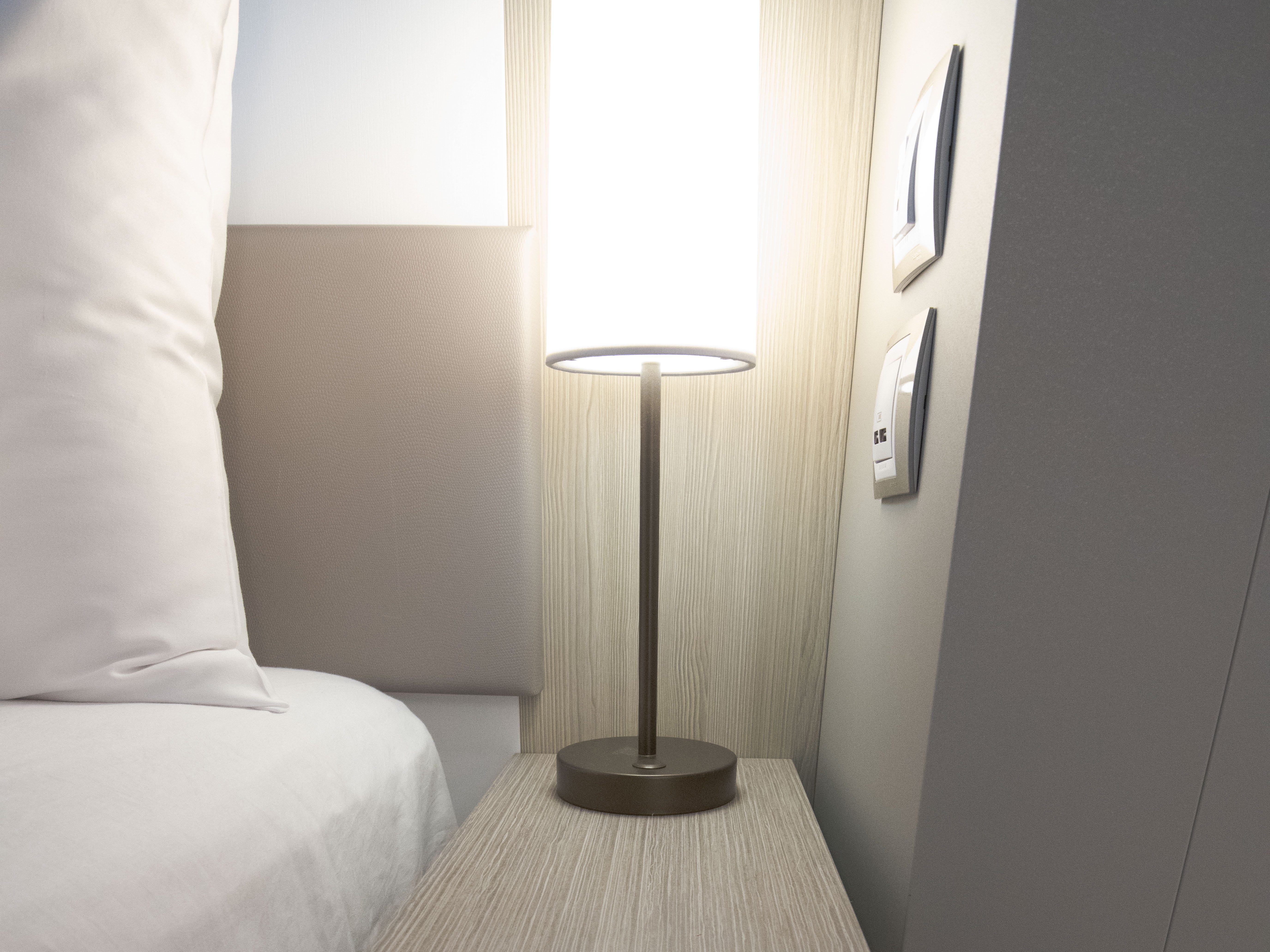 Small tables are located on each side of the bed in Edge Stateroom with Infinite Veranda cabins.