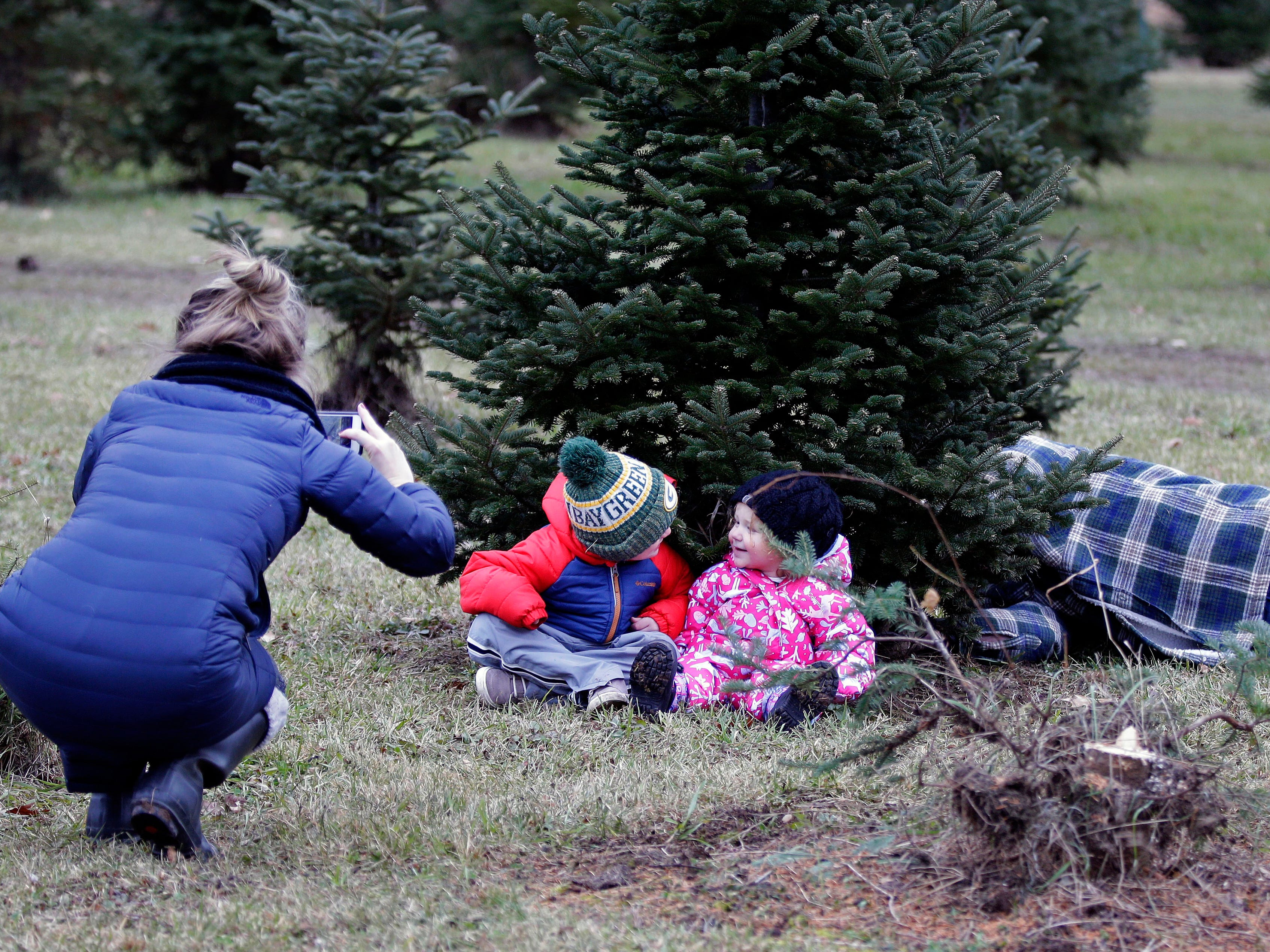 Kirsten Van Asten, tries to record a family moment with her children, Jack and Ivy, but Jack is more interested in watching his father, Brandon, cut the tree down Sunday, November 25, 2018, at the Mosquito Hill Tree Farm in New London, Wis.Ron Page/USA TODAY NETWORK-Wisconsin