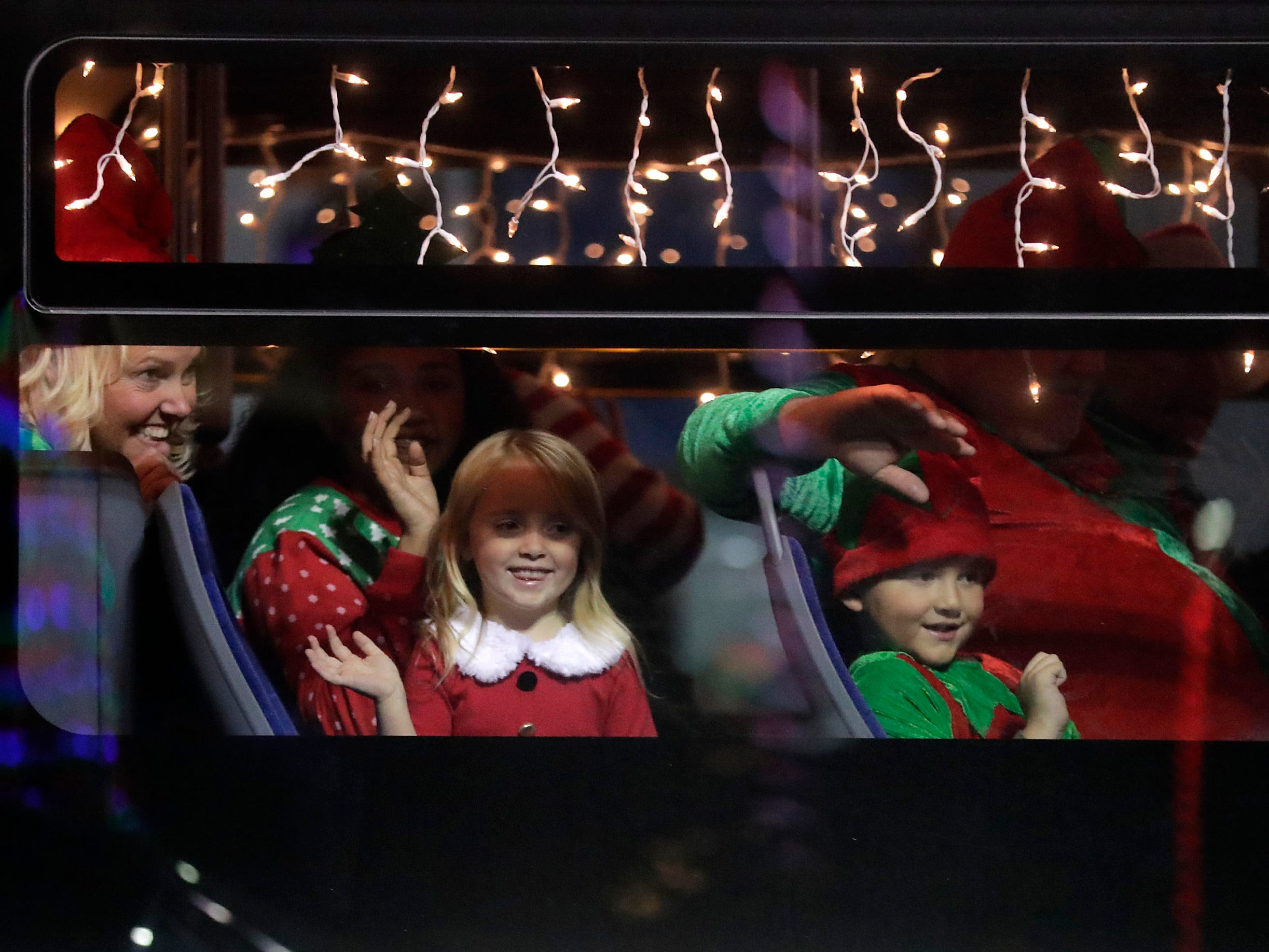 """Riders on the Valley Transit float/bus wave during the 48th Annual Downtown Appleton Christmas Parade on Tuesday, Nov. 20, 2018 in Appleton, Wis. This year's theme was """"Home for the Holidays."""" Wm. Glasheen/USA TODAY NETWORK-Wisconsin."""