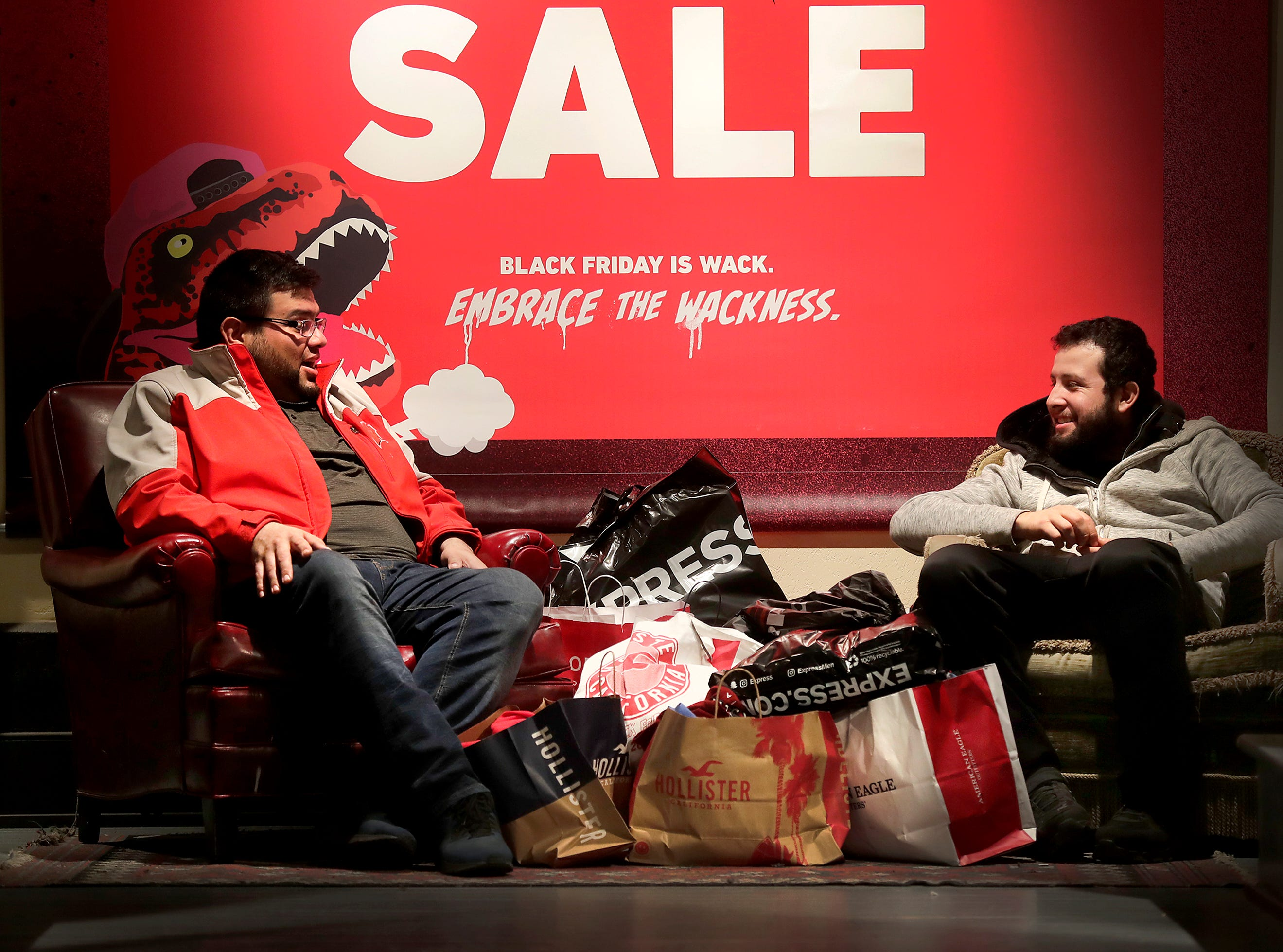 Jesus Martinez, left, and Santiago Camarena wait with their Black Friday purchases while their families shop at Hollister on Black Friday at the Fox River Mall on Friday, Nov. 23, 2018 in Grand Chute, WisWm. Glasheen/USA TODAY NETWORK-Wisconsin.