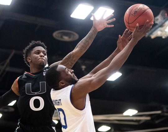 Seton Hall guard Quincy McKnight, right, goes up to the basket past Miami guard Chris Lykes during the Wooden Legacy final.