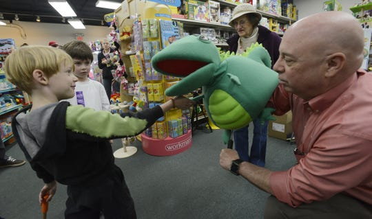 Jeff Hutchins, a writer in Black Mountain, has a new kids book out called Denton the Dragon and he introduces the three-foot tall dragon to (from left)  Frost Maleike, 6, and Jagger Balhar, 7  of Asheville at the Toy Box store on Merrimon in 2013.
