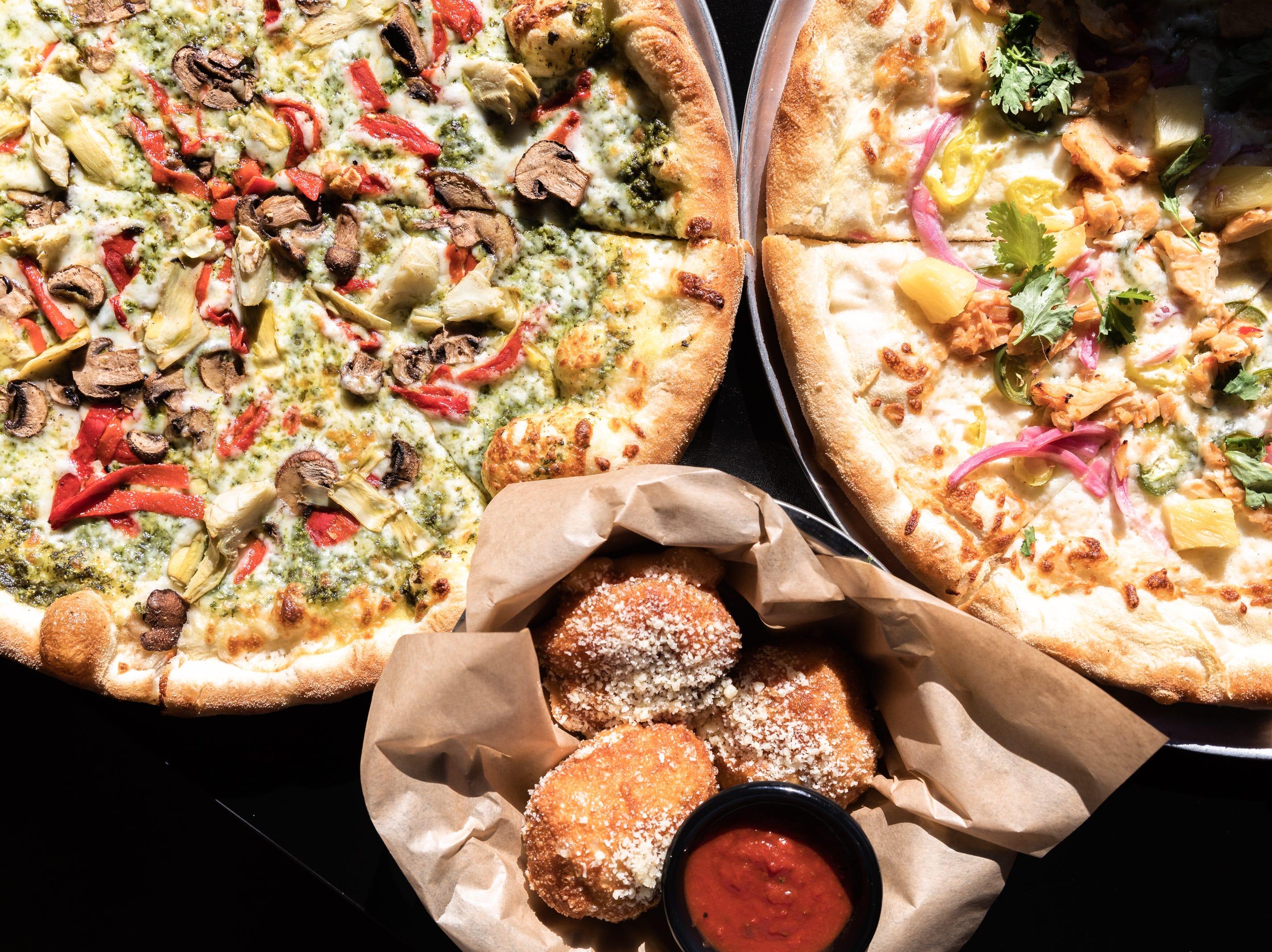 Galactic Pizza's Pesto Artichoke pizza, Bahn Mi pizza and Meat Lovers spaceballs.