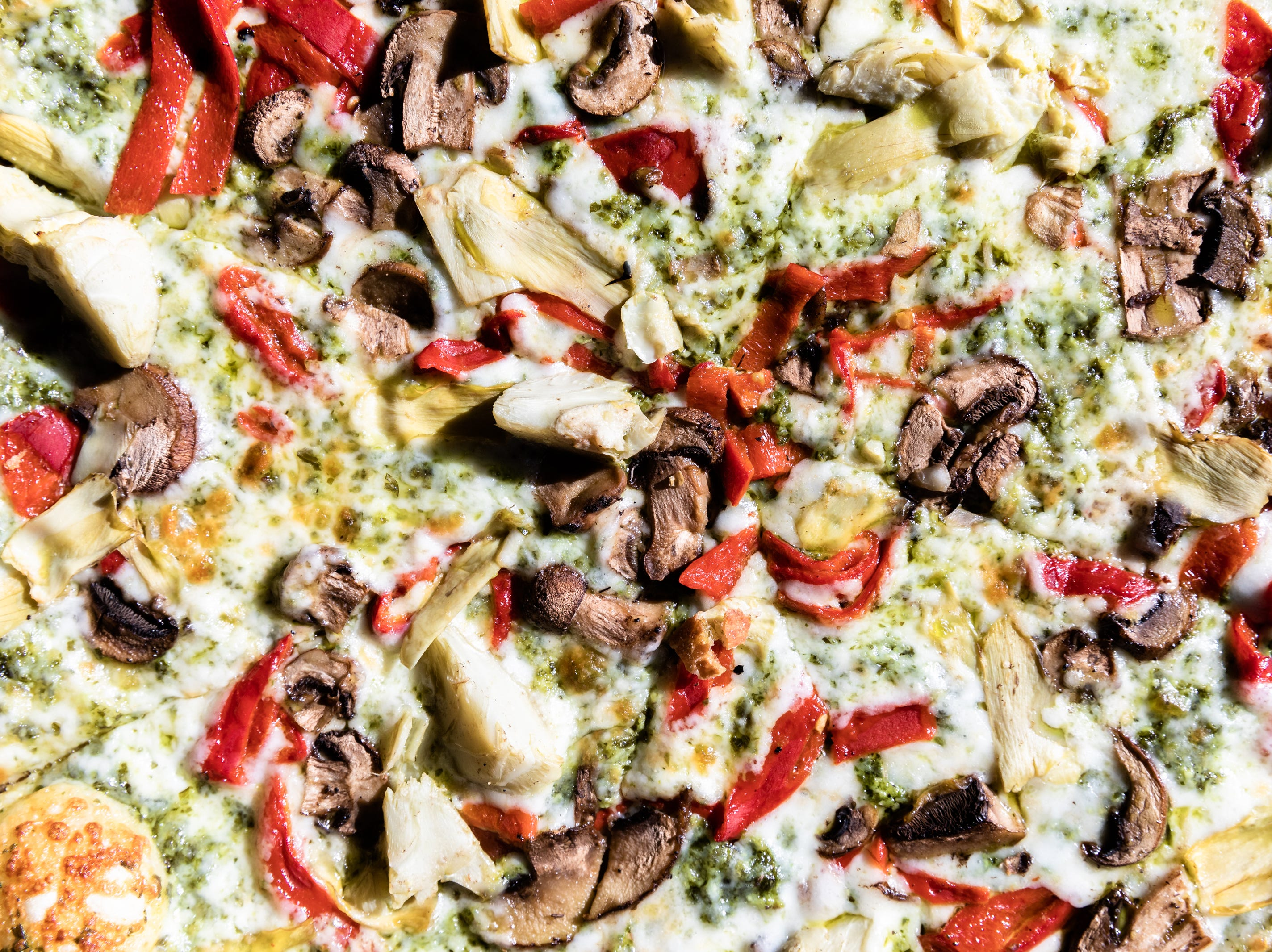 Galactic Pizza's Pesto Artichoke pizza with artichoke, roasted red peppers, mozzarella, mushrooms with house made pesto sauce.