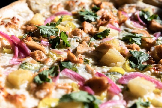 Galactic Pizza's Bahn Mi pizza with grilled sweet chili chicken, pickled red onion, pineapple, jalapeño, banana pepper, mozzarella, provolone, garlic oil and cilantro.