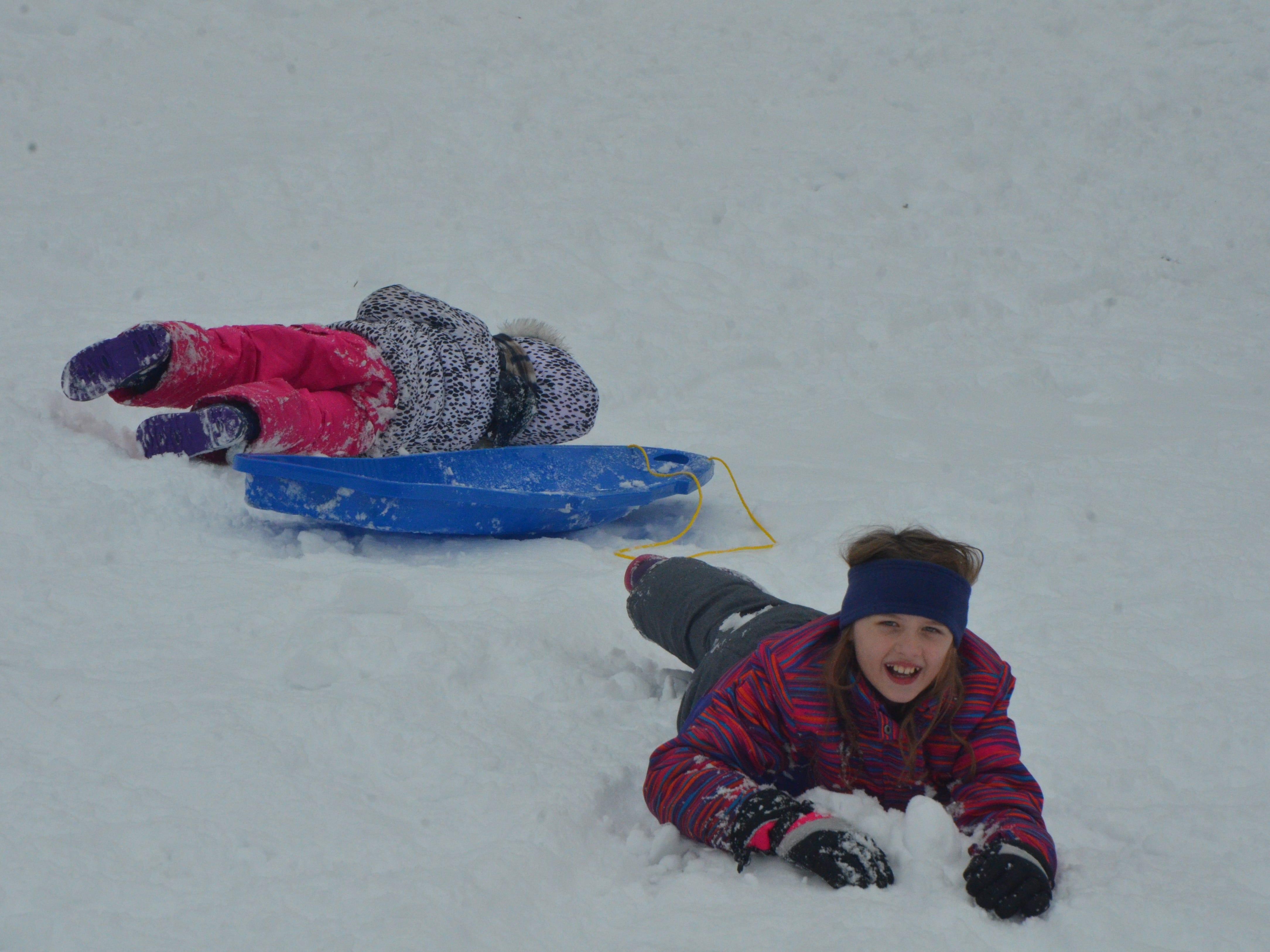 Alexandria Camburn, 11, and Nadia Craft, 4, wipe out while sledding at Leila Arboretum on Monday, November 26, 2018.