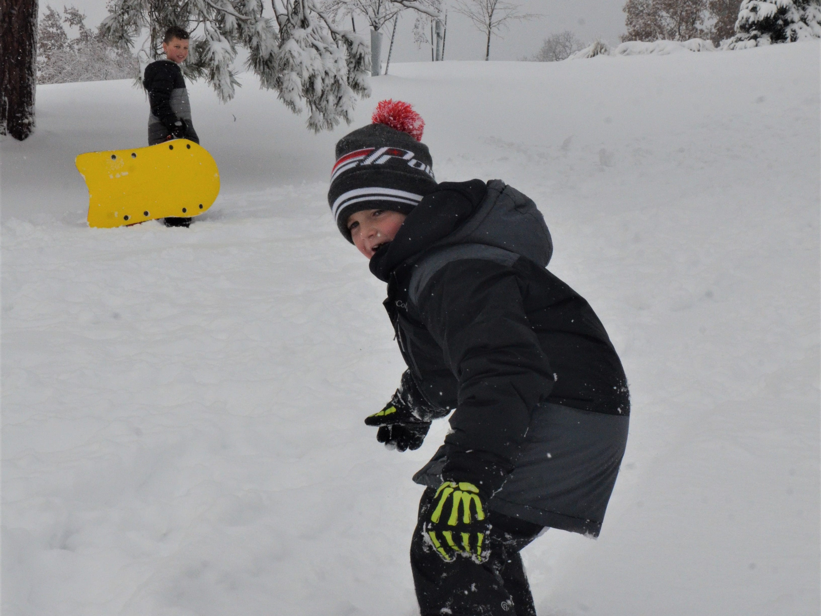 Landon Bennett, 8, rides his snowboard down the hill at Leila Arboretum on Monday, November 26. 2018.