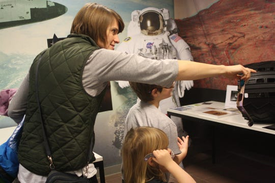 Cathy Apostoleris, of Lima, points out locations on Kopernik's 3-D diagram of Mars to her children, Leander Apostoleris, 7, and Eleni Apostoleris, 4.