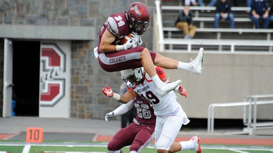 Colgate safety Alec Wisniewski goes airborne to defend.