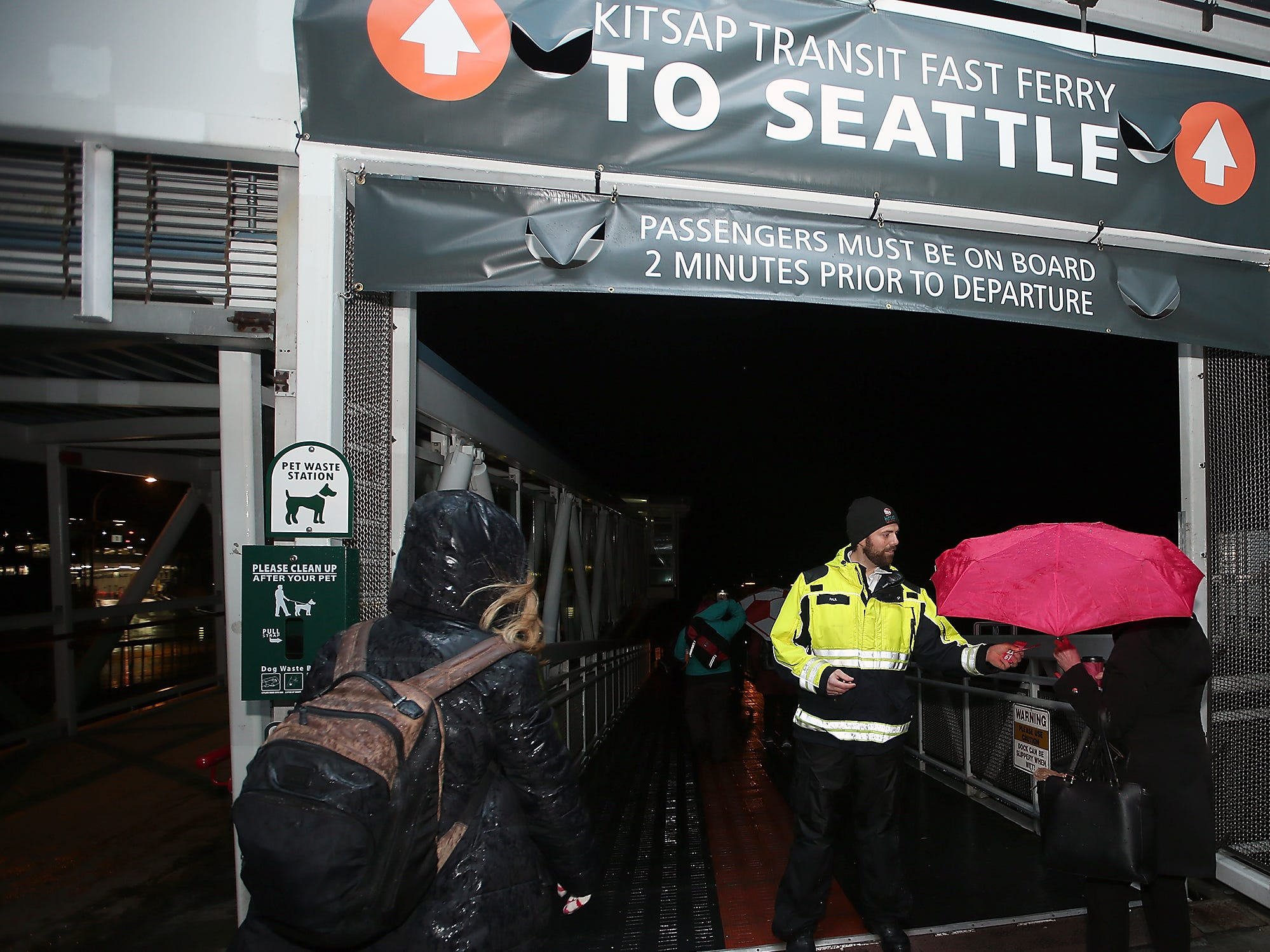 Kitsap Transit Marine Service Ambassador Paul Boudreaux  hands out boarding passes as passengers prepare to make their way down the dock to the M/V Finest for the 7:05 run to Seattle on Monday, November 26, 2018.