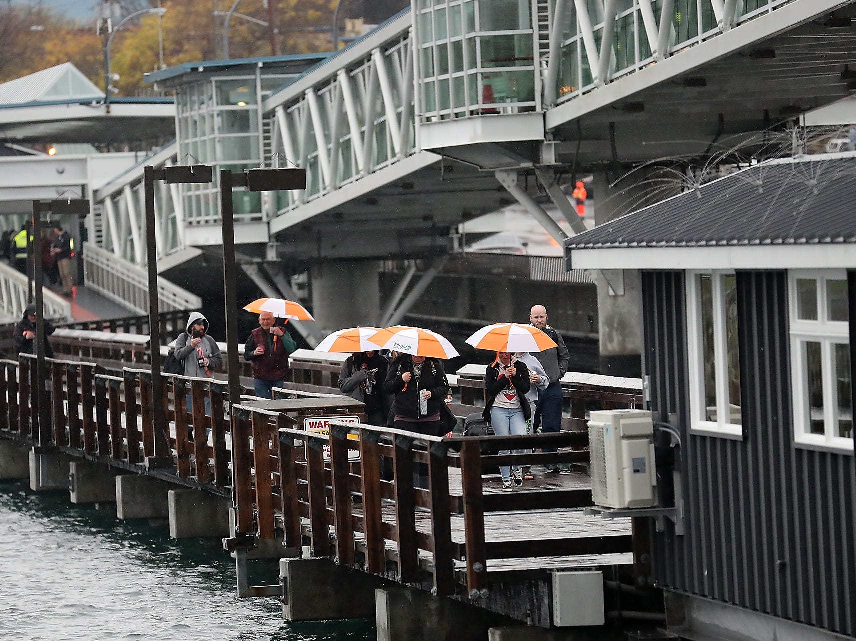 Ferry passengers tote complimentary  Kitsap Transit umbrellas as they head for the 8:45am Fast Ferry sailing from Kingston to Seattle on Monday, November 26, 2018.