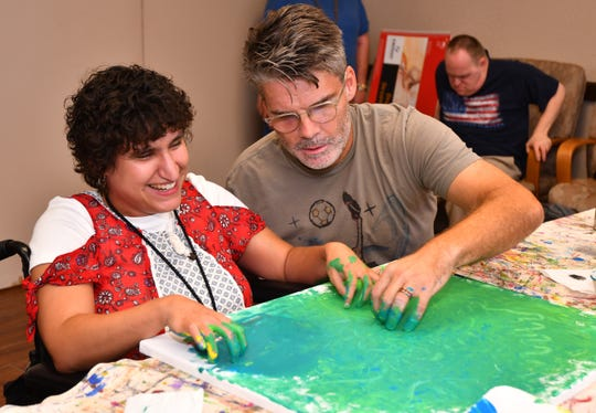 Artist Derek Gores works with Cecelia Rodriguez, who is blind, at Bridges in Rockledge.