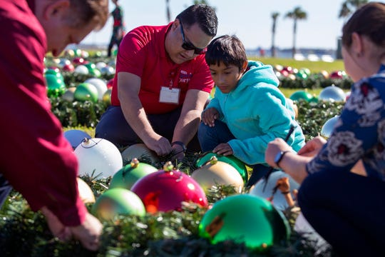 Bobby Rodriguez (left) and Travis Ceniceros, 11, install ornaments on the sections of the new H-E-B Christmas Tree at the Water's Edge Park on Monday, November 26, 2018. The tree features more than 7,000 lights, 2,000 ornaments and a nativity star and is 66-feet tall. It costs about $250,000 and is sponsored by H-E-B. The tree will be the centerpiece for the Harbor Light's festival which is Saturday.