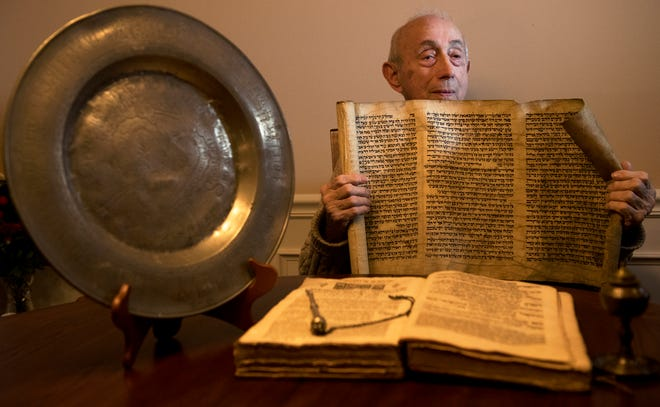 Holocaust survivor Fred Behrend displays a scroll of vintage Hebrew writings as he sits in his Voorhees home with a collection of artifacts that includes a family Seder plate dating to 1710.  Behrend recently reconnected with a childhood friend, Henry Baum, and will reunite with him over the winter in Florida.