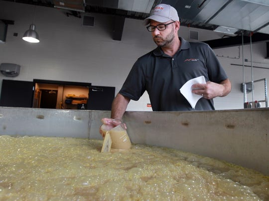 At New Riff Distilling, David Miller draws a sample of bourbon mash from a 5,600-gallon fermenter.