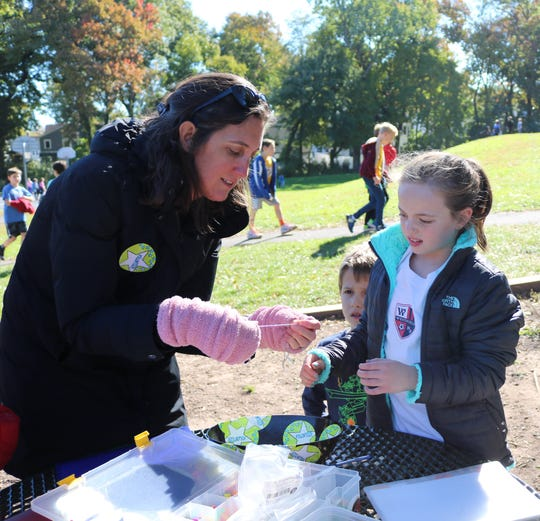 Debi Kapuscinski (left) helps 4th grader Scarlett Goldman prepare a charm necklace to which the student will add as she completes additional laps in the Recess Runners' Club at Washington School.