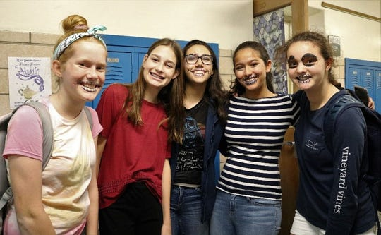 Left to right:  Edison 8th graders Katherine O'Connor, Jessica Currie, Josefina Rios, Maya Dias, and Sophia Narciso paint skeleton smiles on their faces as part of the school's  Dia de la Muertos celebration on Nov. 2.