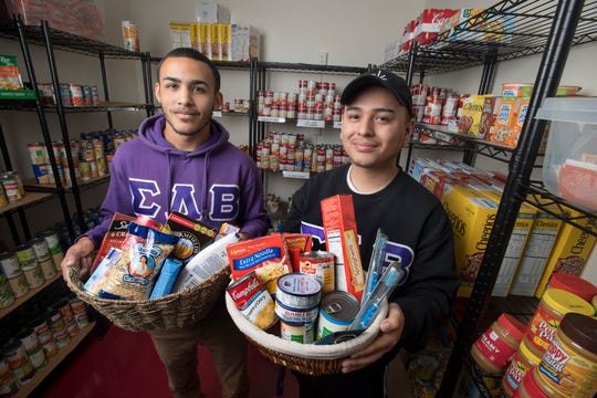 Sigma Lambda Beta Tau Alpha Chapter President Aziel Rosado (left) with Director of Recruitment and fraternity brother Percy Tito in the Student Food Pantry at Off-Campus Living and Community Partnerships.